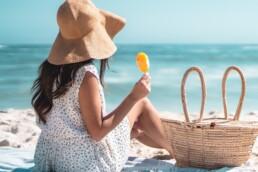 Kobieta siedząca na plaży w kapeluszu przeciwsłoneczym, chroniąca włosy przed słońcem.