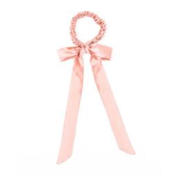 Jedwabna gumka do włosów ze wstążką w kolorze pudrowego różu.